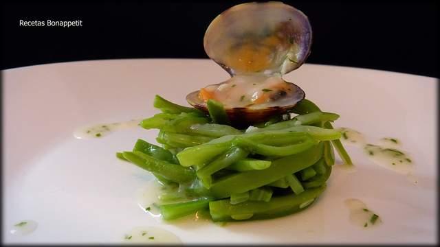 """JUDIAS CON ALMEJAS EN SALSA VERDE Ingredientes (para 4 personas) • 800 gr. de judías verdes frescas • ½ kg. de almejas • 4 dientes de ajo • 4 cucharadas soperas de aceite de oliva virgen extra • 1 cucharada sopera de harina • 3 vasos del agua de cocción de las judías verdes • perejil picado • sal Elaboración: Limpiamos en agua fría las judías verdes, con un cuchillo, cortamos las puntas, si son anchas las cortamos en dos a lo largo. Seguidamente las cortamos en trozos de unos 4 cm. aproximadamente. Cocemos en agua hirviendo con sal durante 10 minutos. Escurrimos (reservamos 2 vasos de esta agua de cocción para elaborar la salsa verde) y las refrescamos en agua fría con hielos para cortarles la cocción. Volvemos a escurrirlas y reservamos. Ahora limpiamos las almejas, es el paso más importante de esta receta. En un bol, con abundante agua con sal introducimos las almejas, las removemos sin golpearlas entre sí. Dejamos 20 minutos y repetimos la misma operación. Una vez están limpias escurrimos y reservamos. Por otro lado, en una sartén al fuego echamos el aceite de oliva junto con el ajo picado finamente. Cuando comience a """"saltar"""" el ajo añadimos la harina y removemos. Seguidamente mojamos con el agua de cocción de las judías y mezclamos para evitar que aparezcan grumos. Dejamos cocer a fuego suave e introducimos las almejas, tapamos y dejamos que se abran. Es importante que una vez estén abiertas retirarlas para que no se pasen de cocción y nos queden cauchosas. Una vez retiradas añadimos las judías a la salsa para calentarlas. Ponemos a punto de sal, espolvoreamos perejil, introducimos nuevamente las almejas y retiramos del fuego. En una fuente colocamos las judías verdes con las almejas en salsa verde."""